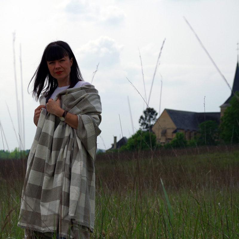 femme dans un champs avec un plaid pur lin sur les épaules