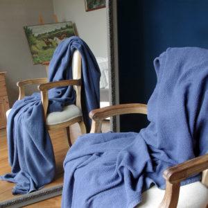 joli plaid en lin lavé couleur bleu tissage chevrons posé sur fauteuil