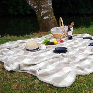 pique-nique repas pris en plein air dans un cadre champêtre et installé par terre avec plaid en pur lin lavé